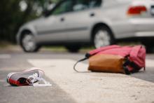 Chaussure et sac à dos sur la route après accident. IntoLaw décrit accident avec délit de fuite en Belgique.