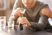 Man met autosleutels en glas alcohol in de hand. IntoLaw over pakkans en ongevallen bij rijden onder invloed.