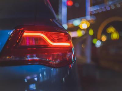Achterlichten van een auto in het donker met mooie feestlichtjes op de achtergrond - IntoLaw