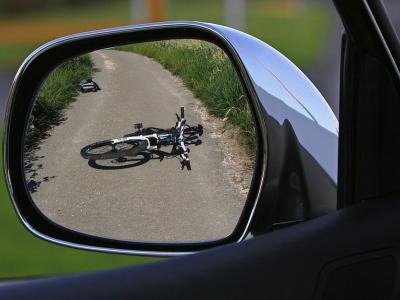 Fiets ligt op de grond na ongeluk met auto, gezien door de zijspiegel van de auto - IntoLaw