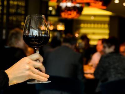 Iemand heft een glas rode wijn tijdens de feestdagen, maar vermijdt alcoholcontrole - IntoLaw