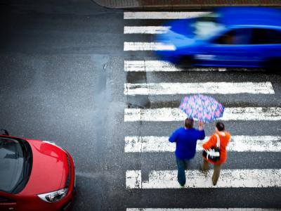 Auto rijdt door terwijl voetgangers oversteken aan zebrapad. IntoLaw waarschuwt voor boetes van minimum 174 euro.