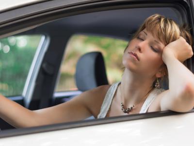 Jonge vrouw zit slapend achter het stuur van haar wagen - IntoLaw