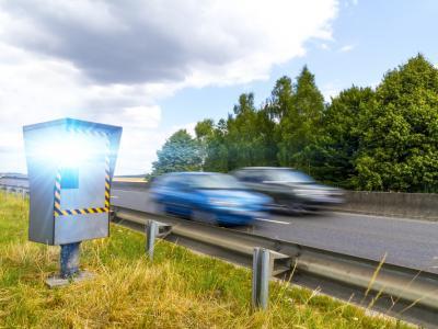 Een flitscamera flitst een blauwe en zwarte auto. IntoLaw stelt overdreven snelheid aan de kaak.