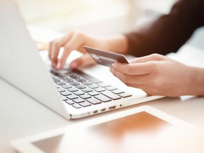 Persoon met bankkaart achter de computer betaalt verkeersboetes online - IntoLaw