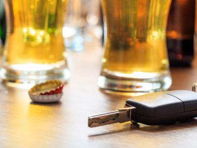 Glazen bier en autosleutel op tafel. IntoLaw over rijden onder invloed bij mannen.