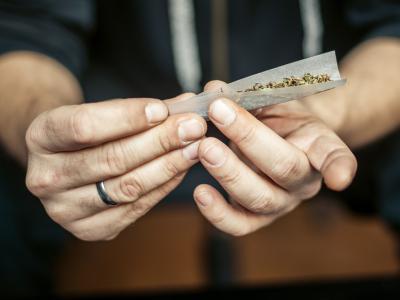 IntoLaw gaat de financiële gevolgen na van rijden onder invloed van drugs. Op de foto ziet men twee handen die een joint rollen.