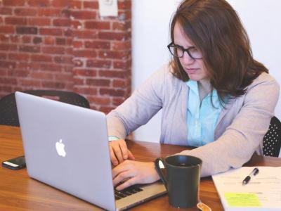 Jonge vrouw leest kwaad e-mail met valse boetes op een laptop met thee naast haar - IntoLaw